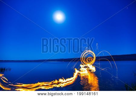 Colorful Fireworks over Lake at night. Moon, blue sky, bright flash, explosion.