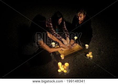 Woman spiritualists communicating with ghosts through spiritual board