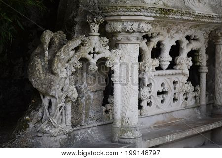 Detail in the park - old stone statue of heron in manueline style, Quinta da Regaleira Palace in Sintra, Portugal.