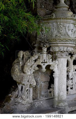 Detail in the park - old stone statue of heron, Quinta da Regaleira Palace in Sintra, Portugal.