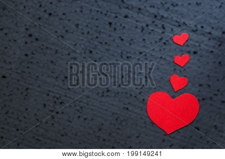 Valentines day background - bright red hearts on a black background. Place for writing text. Copy Space