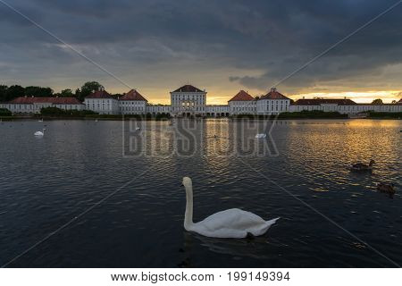 Dramatic scenery of Nymphenburg palace in Munich Germany. Sunset after the sorm. White swans and duks swimming in pond in front of the palace.