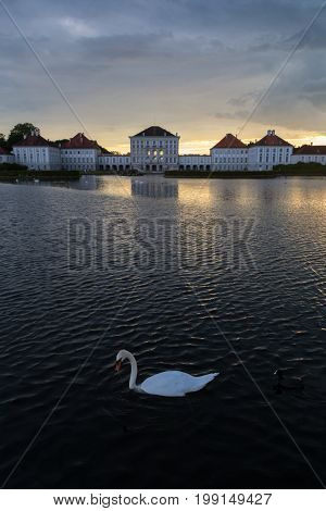 Dramatic scenery of Nymphenburg palace in Munich Germany. Sunset after the sorm. White swan swimming in pond in front of the palace.
