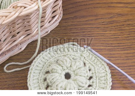 Work place with Vines basket and handmade crochet doily coaster and a hook. Cotton yarn for knitting