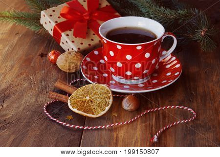 Christmas cup of tea with a gift, orange, nuts and Christmas decor