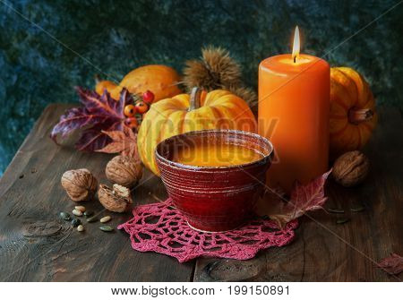 Autumn pumpkin soup with seeds on a wood table autumn decor with candle