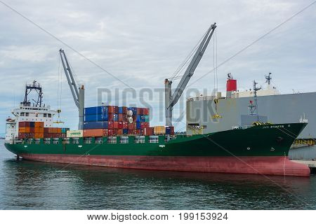 Labuan,Malaysia-July 14,2017:Cargo ship,full of shipping containers in the port of Labuan island,Malaysia.
