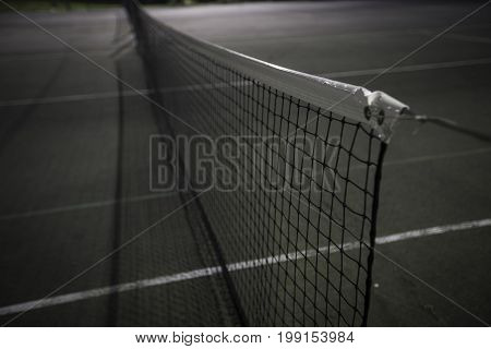 Blue and green tennis court net at night