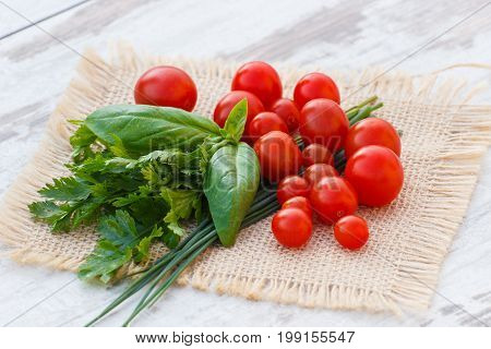 Red Cherry Tomatoes With Green Parsley And Basil On Jute Canvas