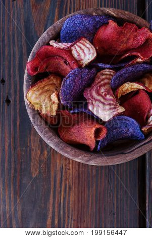 Vegetable potatoes and blue potatoes chips and beetroot chips served as a finger food snack in a wooden bowl