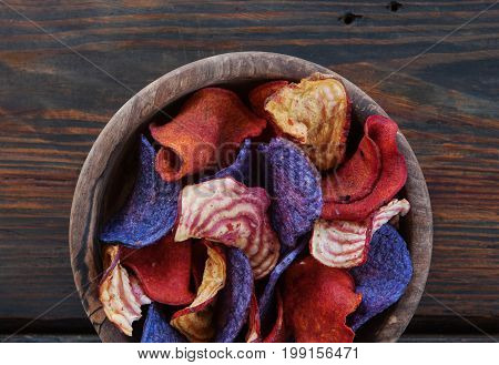 Crunchy organic dry vegetable chips and beetroot chips served as a finger food snack in a wooden bowl