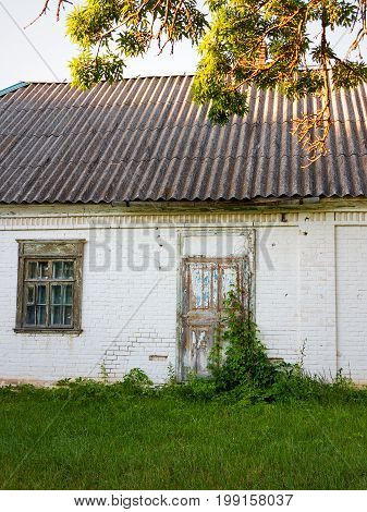 Old Barn White Brick Under The Open Sky In Village. Wooden Door With Iron Bolts And Lock Is Overgrow
