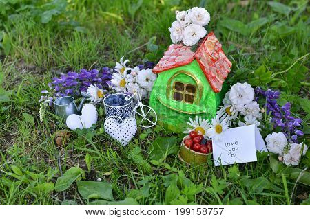 Small house with note love you, summer berries and flowers. Lovely miniature house for greeting cards, wedding or birthday concept, real estate, downsizing, home ownership. Vintage summer background