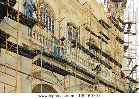February 2012: Cuba Havana architectural renovation Havana Cuba. some bricklayers are engaged in a restoration work of one of the many historic buildings of the capital