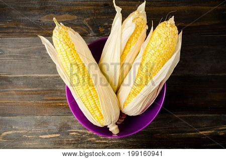 Ripe sweet corn in the purple bowl on wooden background for eating