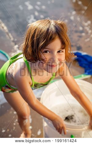 A toddler with a sweet and slightly impish expression looks at the camera as she leans over a two gallon bucket full of soapy water. She is wearing a swimsuit and there is a hose and a rag on the ground in the background.