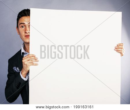 pretty cool european businessman holding empty white plate smiling, making advert, business people concept