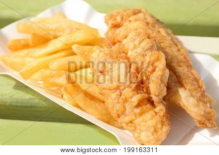 Tasty fried fish and chips on wooden bench