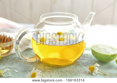 Glass teapot with tasty chamomile tea on color wooden table