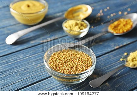 Delicious mustard seeds in bowl on wooden table