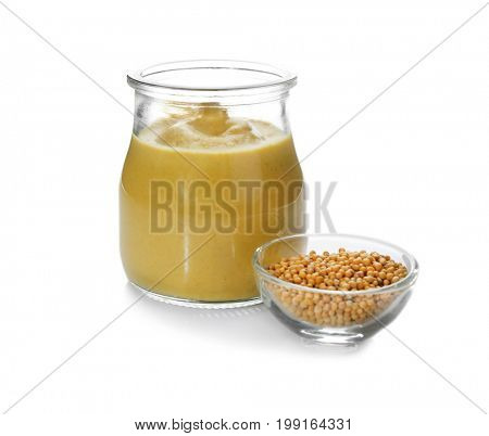 Mustard seeds in bowl and jar with delicious sauce on white background