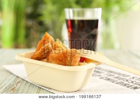 Fried fish and chips with glass of juice on wooden table