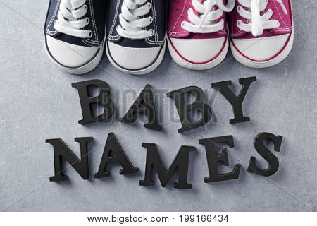 Text BABY NAMES and shoes on gray background