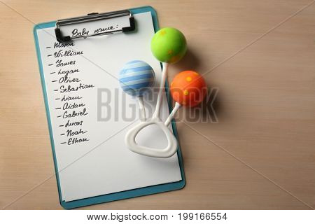 List of baby names and rattle on wooden background