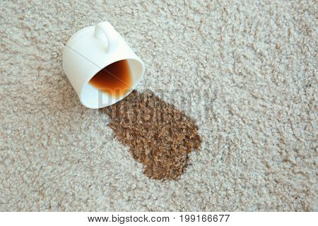 Cup of coffee spilled on white carpet