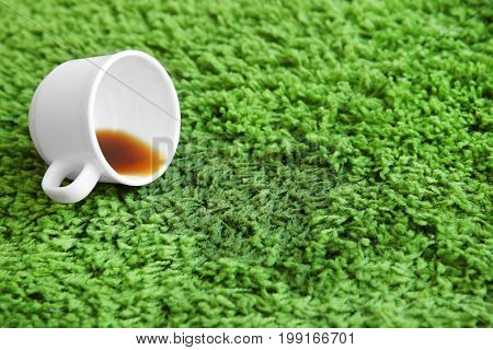 Cup of coffee spilled on green carpet
