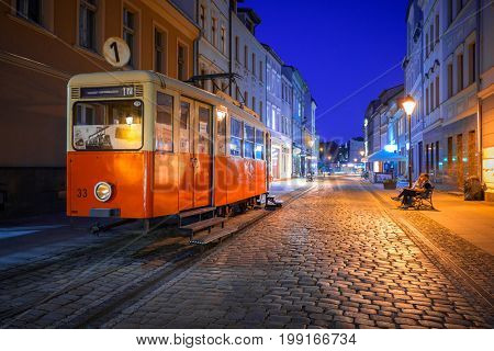 BYDGOSZCZ, POLAND - AUGUST 1, 2017: Bydgoszcz city with old tram used as tourist information at night, Poland. Bydgoszcz is the city with beautiful neo-gothic and neo-baroque architecture.