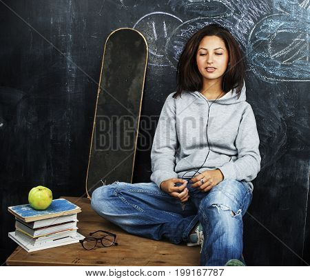 young cute teenage girl in classroom at blackboard seating on table smiling, modern hipster concept, lifestyle people