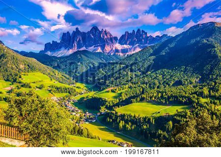 The sun illuminates grandiose crenellated rocks of Tirol. Small picturesque village in Alpine meadows. The Dolomites. The concept of eco-tourism