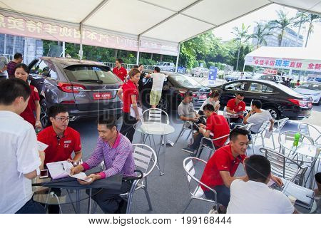 Dongguan, Guangdong, China - August 7, 2017: Car salespersons talking with prospective Chinese brand automobile buyers at Dongguan car exhibition