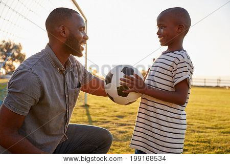 A boy holds a football while playing with his dad