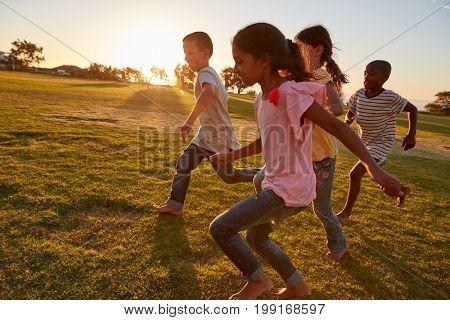 Four children running barefoot in a park