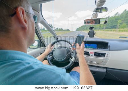 Man using phone while driving the car. Risky driving behaviors concept
