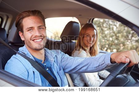 Young couple going on holiday in a car smiling to camera