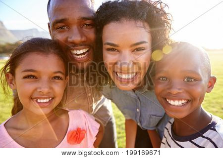 Laughing black family outdoors, close up, back lit portrait