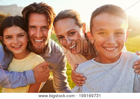 Portrait of happy white family embracing outdoors, backlit