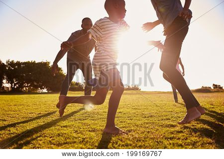 Young black family playing in a field in Summer