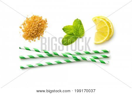 Mojito ingredients. Lemon, mint and cane sugar isolated on white background. Sweet sugar, mint leaves, lemon and striped straw.