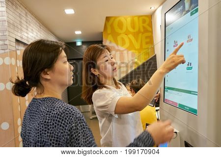 BUSAN, SOUTH KOREA - CIRCA MAY, 2017: women use ordering kiosk at McDonald's restaurant. McDonald's is an American hamburger and fast food restaurant chain.