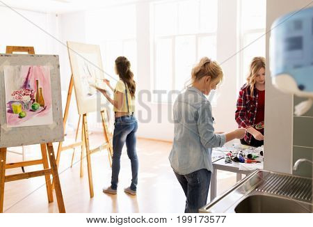 creativity, education and people concept - group of woman artists or students with colors painting still life pictures on easels at art school studio