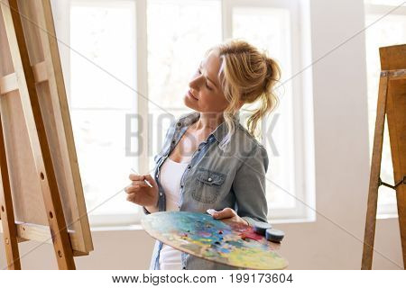 art school, creativity and people concept - happy woman artist with easel, paint brush and palette painting at studio