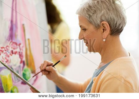 art school, creativity and people concept - happy senior woman artist with easel, paint brush and palette painting at studio