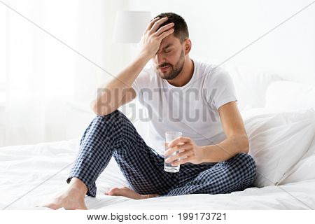 people, bedtime and rest concept - man in bed with glass of water at home