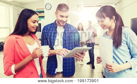 business, communication, startup and people concept - happy multiracial creative team or students with tablet pc computer and papers on coffee break talking at office