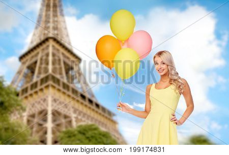 travel, tourism and summer holidays concept - happy young woman or teen girl in yellow dress with helium air balloons over paris eiffel tower background