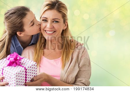 people, holidays and family concept - happy girl giving birthday present to mother over lights background